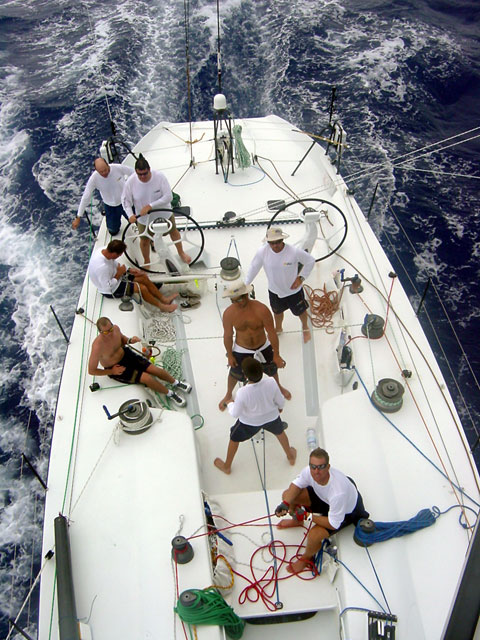Afternoon watch in the trades. From the stern, Ed talking about the weather, Philippe steering, Madro mainsheet, Kevin on standby grinding the mainsheet, Dave trimming the kite, Tony and Shark grinding the kite, Freddy tailing Doogie up the mast.