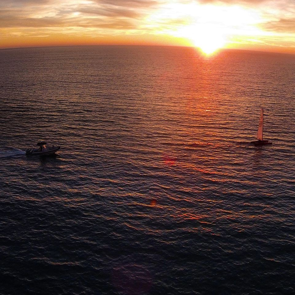 Philippe Kahn sailing the A-Cat. Photo was taken with a drone, and shows the chase boat in the light air and sunset.